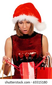 Surprised christmas girl holding shopping bags wearing Santa hat. Isolated on white background.