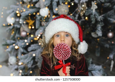 Surprised christmas girl in a Santa hat and red dress holding a candy cane. Happy Christmas and New Year.