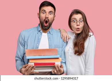 Surprised classmates or teacher and student gaze in stupor, read literature, hold textbooks, stand closely, have bugged eyes, isolated over pink background, share ideas, terrified with shocking news