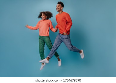 Surprised couple in orange sweatshirts jumping on isolated background. Shocked emotional man in red sweater and woman in green denim pants move on blue background