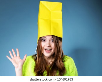 Surprised crazy woman bright vivid colour sweater with paper shopping bag on head blue background. Sales and discounts concept.
