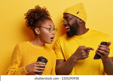Surprised curious dark skinned woman looks at screen of boyfriends cellular, reads online post with interesting content, excited with smartphone or app features, isolated over yellow background.