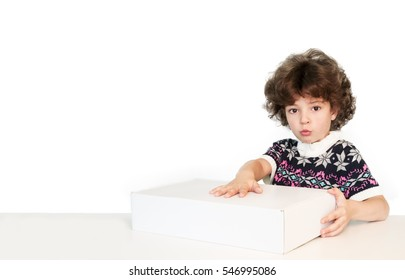 Surprised cute boy put his hand on the white box looking at the camera. White background.