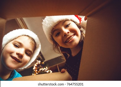 Surprised cute children girl and boy opening a Christmas present. Little kid having fun near decorated tree indoors.  Happy  holidays and New Year.
