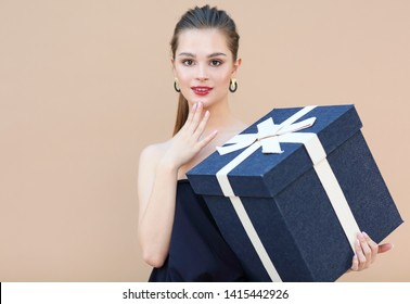 Surprised cute girl in navy blue clothes holding big gift box isolated on beige