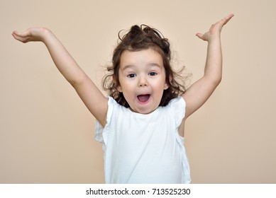 Surprised cute young girl with hands up