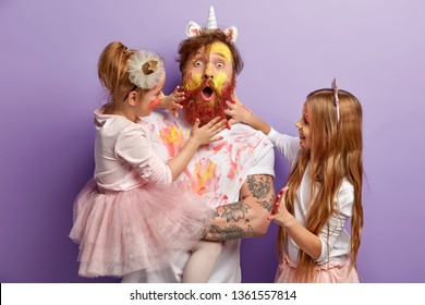 Surprised dad and two girls play together at home, paint faces with watercolours, have fun, show hands painted in bright colours, isolated over purple background. Family portrait. Fatherhood
