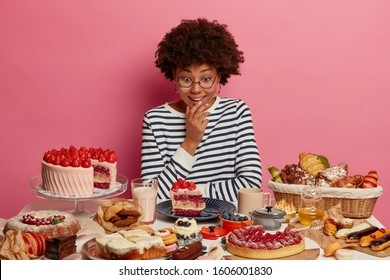 Surprised dark skinned woman looks with temptation at delicious piece of cake, dressed in striped jumper, poses at table with tasty freshly baked confectionery, wants to taste everything at same time