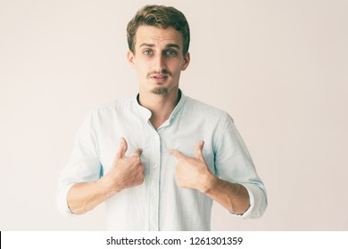 Surprised and doubted guy in white casual shirt asking Who, Me. Handsome young Caucasian man with upset questioning face pointing fingers at himself. Surprise or selection concept