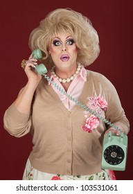 Surprised drag queen holding telephone over maroon background