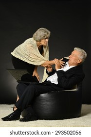 Surprised elderly couple looking on laptop screen