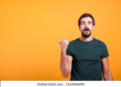 Surprised emotional adult man pointing at the copyspace which in available for your text, advertisement or promotions. Amazement and enthusiasm concept
