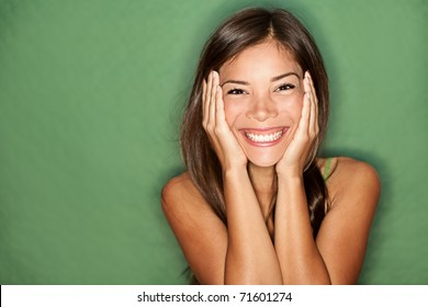 Surprised excited woman on green background. Cheerful multiracial Asian / Caucasian female model joyful.