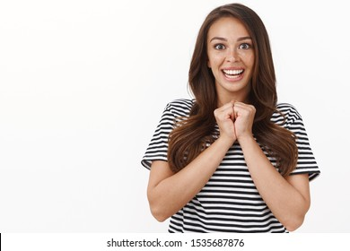 Surprised excited young cute girl clench hands together, smiling amused, cannot believe she lucky winner, triumphing, look with adoration and joy camera, cannot wait receive award, white background