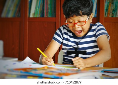 Surprised expression of the asian boy during use yellow pencil coloring the art work