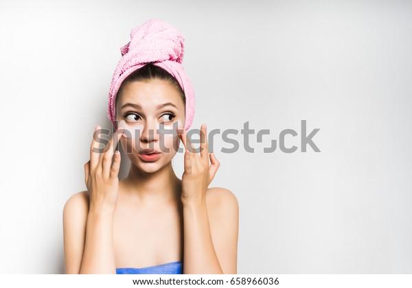 驚いた顔の女性が目の下の斑点に触れる。