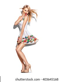 Surprised Fashion model Girl full length portrait dressed in short white dress and beige high-heeled shoes. Blowing blonde hair. Beautiful young woman posing in studio, emotions, looking back