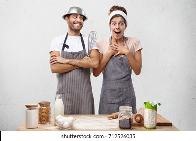 Surprised female cooker not believing that she won culinary competition, looking with great astonishment into camera, being happy to show great results and her friend who supports her helping cooking