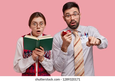 Surprised frightened bearded man eats delicious apple, points at camera with amazed expression, stupefied lady holds textbook, keeps mouth opened, notices something horrified, isolated on pink