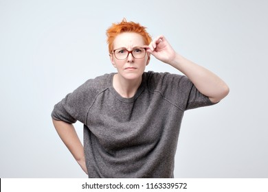 Surprised frustrated mature woman with red hair. She has problems with eyesight. She straightens her glasses trying to see the text