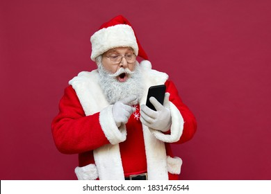 Surprised funny amazed old bearded Santa Claus wearing costume holding cell phone using mobile app on smartphone shocked by Christmas promotion, xmas applications ads isolated on red background.