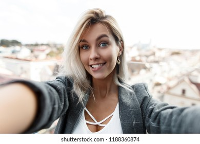 Surprised funny beautiful young woman with a smile in a vintage suit doing selfie on camera in the city. Girl blogger travels in the city and shoots