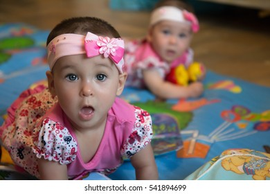 Surprised funny infant sisters, twin baby girls