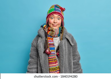 Surprised funny teenage girl wears knitted hat wide scarf and fur coat dresses for winter weather being shocked by something unexpected poses against blue background. Season fashion lifestyle concept