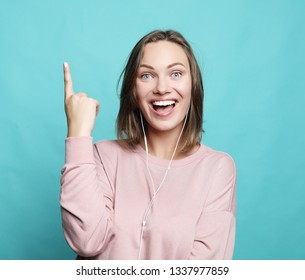 Surprised funny woman showing empty copy space with her finger. Happy girl pointing, looking at camera.