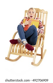 surprised girl with book in hand. Cute girl sitting in a comfortable rocking chair and reading a book. surprised face. isolated on white background