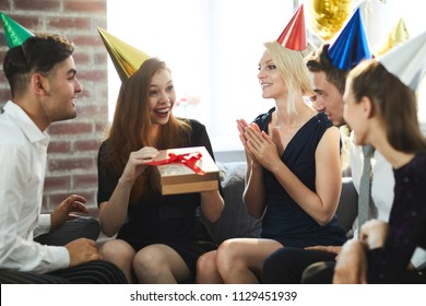 Surprised girl with gift-box saying thanks to her friends while going to open it at birthday party