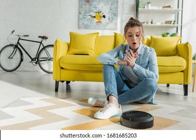 surprised girl looking at robotic vacuum cleaner on carpet in living room