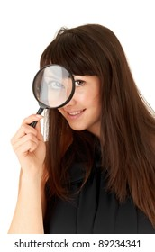 Surprised girl looking through magnifying glass