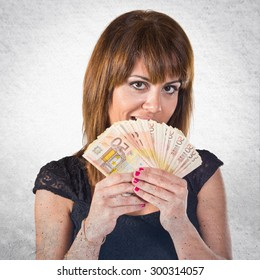 Surprised girl with a lot of money over grey background