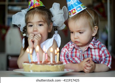 Surprised girl near the candle on her birthday cake with her brother on the background, focus on the girl, happy birthday concept