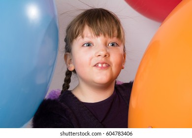 Surprised girl on a background of multicolored large rubber balls