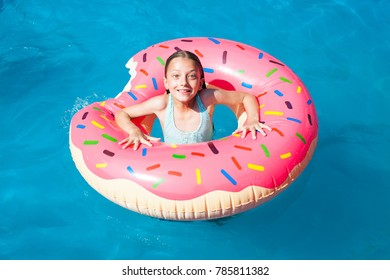 Surprised girl on a colorful inflatable donut in a  swimming pool.