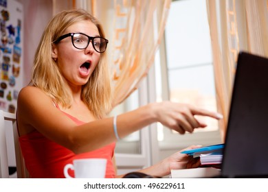 Surprised girl with open mouth shows finger on laptop. Portrait indoor