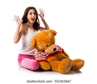 Surprised girl with pajamas and playing with stuffed animal