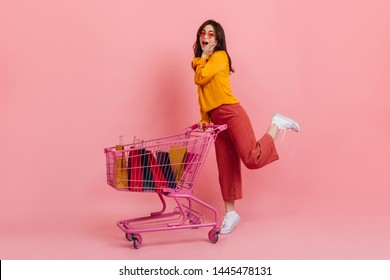 Surprised girl in pink culottes posing with trolley full of multi-colored packages with new clothes