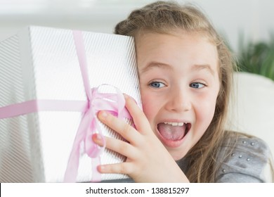Surprised girl shaking a present to guess whats inside