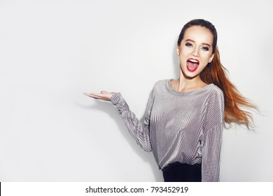 Surprised girl showing empty copy space on open hand palm for text. Woman surprise showing product. Beautiful girl with long hair pointing to the side . Presenting your product. Pretty girl with make