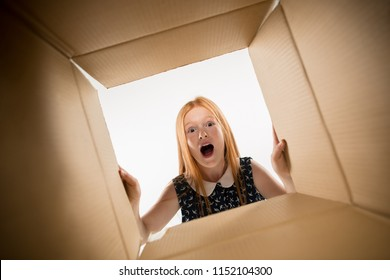 The surprised girl unpacking, opening carton box and looking inside. The package, delivery, surprise, gift lifestyle concept. Human emotions and facial expressions concepts