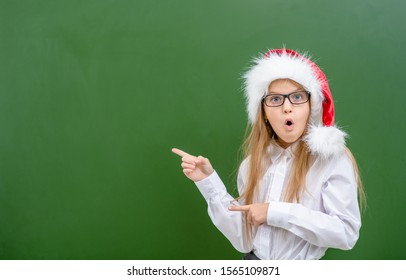 Surprised girl wearing a red christmas hat points away on empty chalk board. Space for text