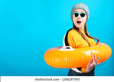 Surprised girl in winter clothes with inflatable orange circle for swimming on blue background. Concept summer vacation.