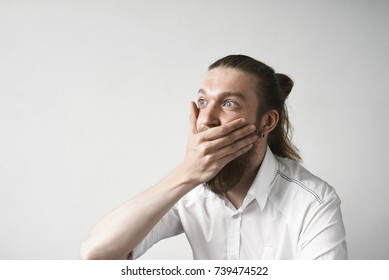 Surprised good looking young man with stylish heavy beard and hair bun covering mouth with hand, restraining himself while being asked to keep some shocking astonishing information a secret