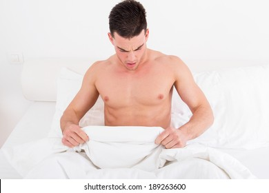 surprised half naked young man in bed  looking down at his underwear at his penis under white covers sheet in bedroom. Concept photo of male sexuality and man sex problems, domestic atmosphere.
