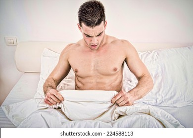 surprised half naked young man in bed  looking down at his underwear at his penis under white covers sheet in badroom. Concept photo of male sexuality and man sex problems, domestic atmosphere.