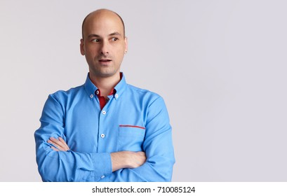 surprised handsome bald man looking side. Isolated on grey with copy space