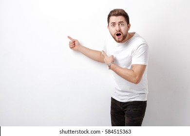 surprised handsome man with beard pointing copy space. young man